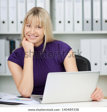 Portrait of confident businesswoman with laptop at office desk