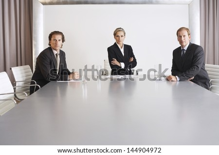 Portrait of confident businesswoman with male colleagues in conference room - stock photo
