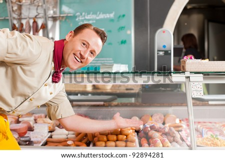 Portrait of confident butcher presenting fresh meat at his shop