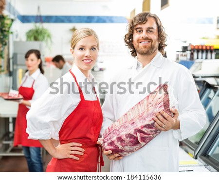 Portrait of confident butchers with meat package standing in store