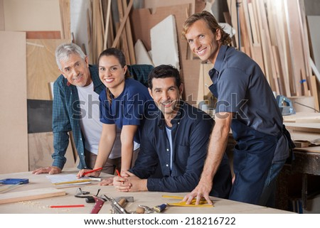 Portrait of confident carpenters working at table in workshop - stock photo
