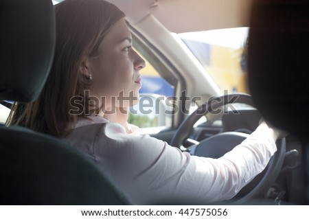 Portrait of confident caucasian woman with phone in car - stock photo