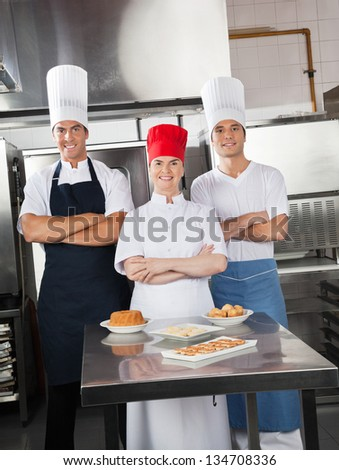 Portrait of confident chefs with sweet dishes on commercial kitchen counter - stock photo