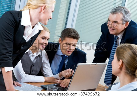 Portrait of confident co-workers looking at laptop monitor while pretty female explaining something