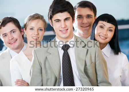 Portrait of confident co-workers with male leader in front of them