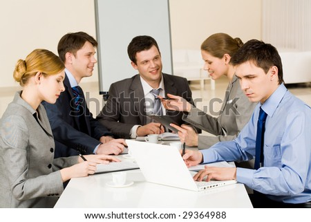 Portrait of confident colleagues working while confident woman sharing her idea with co-workers on background