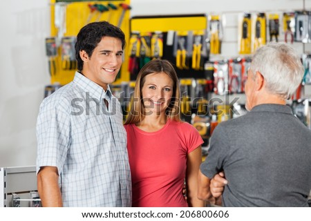 Portrait of confident couple with senior man in hardware shop