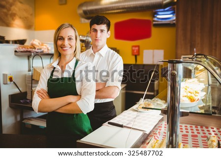 Portrait of confident coworkers by display cabinet in bakery - stock photo