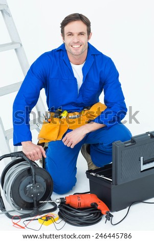 Portrait of confident electrician with tools over white background