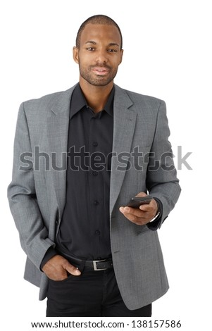 Portrait of confident elegant businessman with cellphone handheld, texting, looking at camera, isolated on white. - stock photo