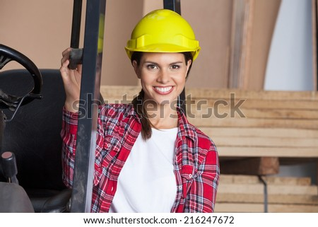 Portrait of confident female architect in hardhat by forktruck in workshop - stock photo