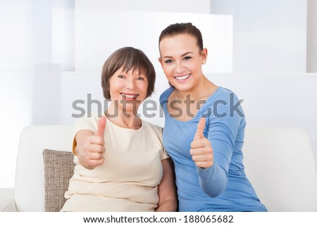 Portrait of confident female caregiver and senior woman showing thumbs up at nursing home - stock photo