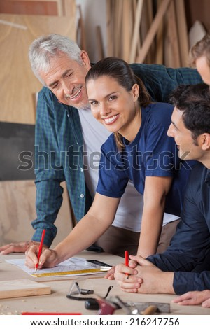 Portrait of confident female carpenter working on blueprint with colleagues at table in workshop - stock photo