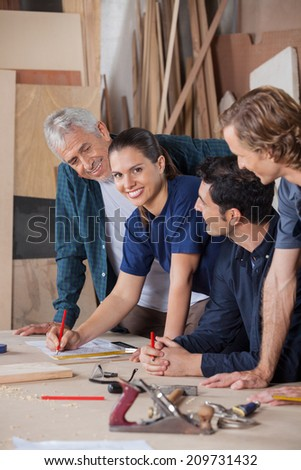 Portrait of confident female carpenter working with colleagues at table in workshop - stock photo