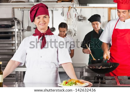Portrait of confident female chef with colleagues cooking in commercial kitchen - stock photo