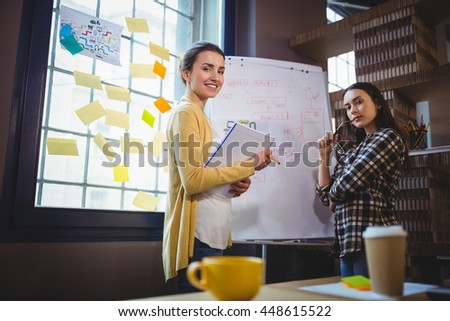 Portrait of confident female colleagues standing by whiteboard in creative office - stock photo