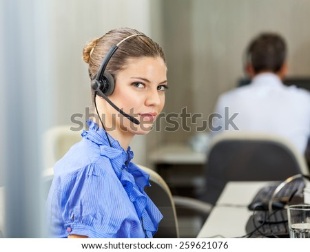 Portrait of confident female customer service representative wearing headset with colleague working in background at call center - stock photo