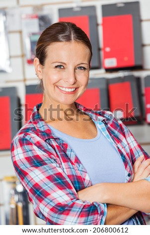 Portrait of confident female customer with arms crossed standing in hardware shop