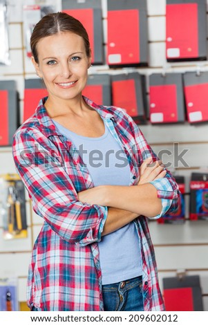Portrait of confident female customer with arms crossed standing in hardware store - stock photo