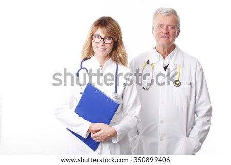 Portrait of confident female doctor holding in her hand a clipboard while standing with senior specitalist doctor at white background.