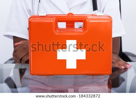 Portrait of confident female doctor with first aid kit at desk in hospital - stock photo