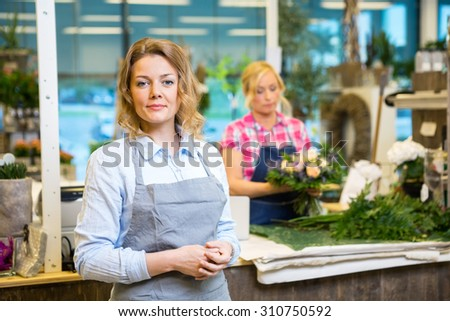 Portrait of confident female florist with colleague working in background at shop - stock photo