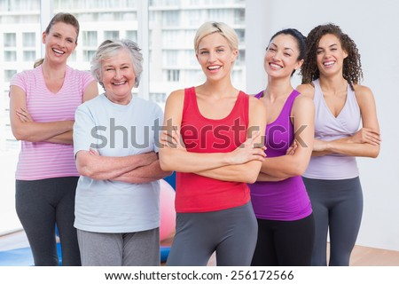 Portrait of confident female friends standing arms crossed in gym - stock photo