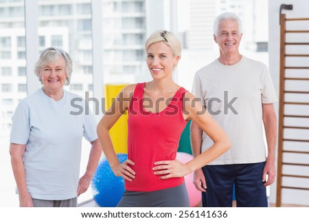 Portrait of confident female instructor with senior couple in gym - stock photo
