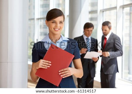 Portrait of confident female looking aside with working colleagues at background - stock photo