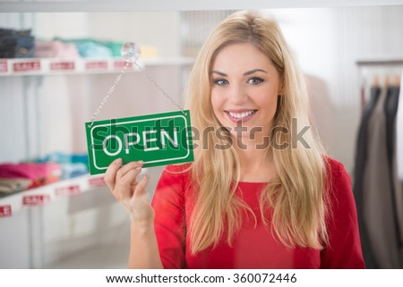Portrait of confident female owner holding open sign in clothing store - stock photo