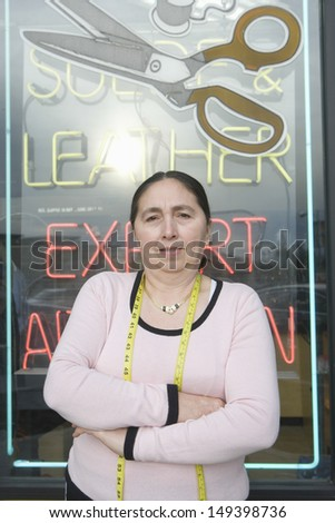 Portrait of confident female owner with arms crossed standing against laundry sign - stock photo