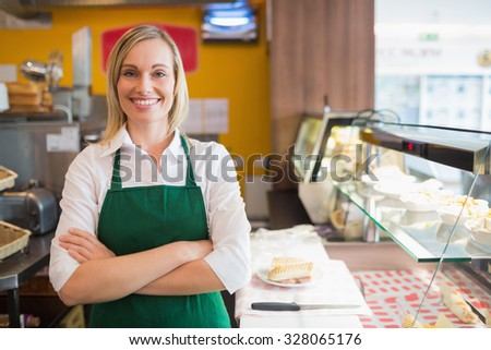 Portrait of confident female shop owner standing by display cabinet in bakery