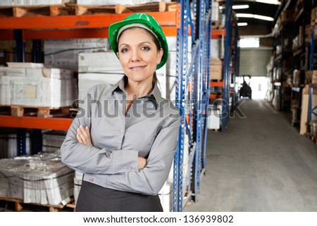 Portrait of confident female supervisor with arms crossed at warehouse - stock photo