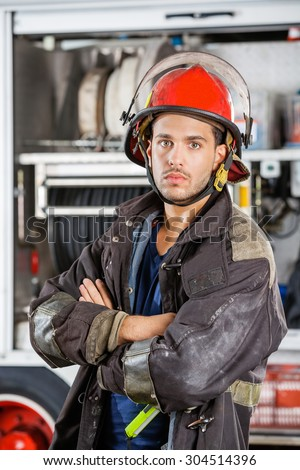 Portrait of confident firefighter standing arms crossed against firetruck at station - stock photo