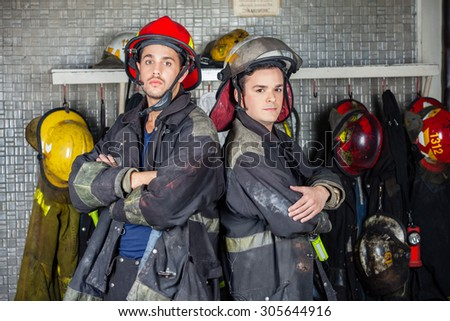 Portrait of confident firefighters standing arms crossed at fire station - stock photo