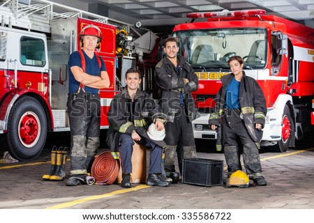 Portrait of confident firefighters with equipment against trucks at fire station - stock photo