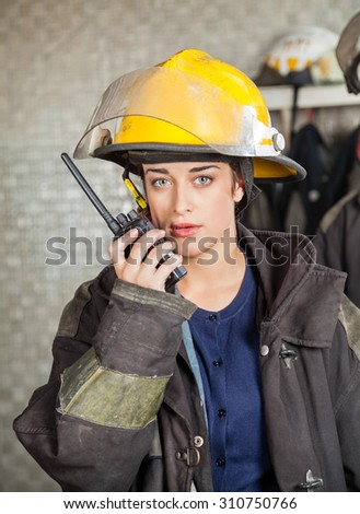 Portrait of confident firewoman using walkie talkie at fire station - stock photo