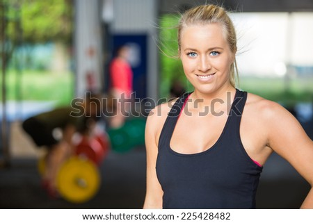 Portrait of confident fit woman smiling while standing in Gym - stock photo