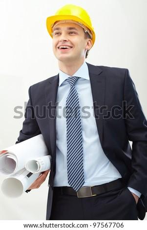 Portrait of confident foreman in helmet holding blueprints - stock photo