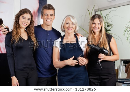 Portrait of confident hairdressers standing together at salon - stock photo