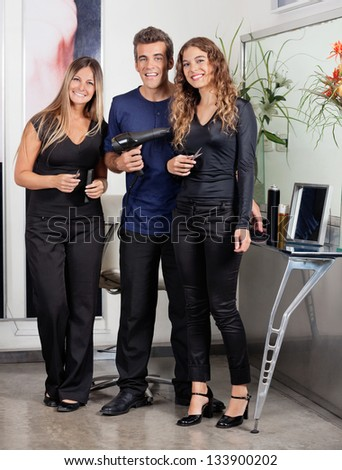 Portrait of confident hairstyling team standing together at beauty parlor - stock photo