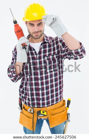 Portrait of confident handyman holding drill machine on white background - stock photo