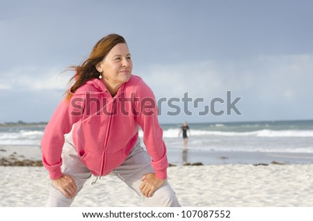 Portrait of confident, healthy and sporty fit attractive looking mature woman in pink sweater, at beach, with isolated storm clouds and wild ocean as background and copy space. - stock photo