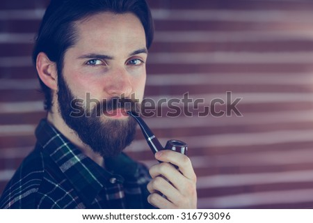 Portrait of confident hipster with smoking pipe against brick wall - stock photo