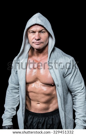 Portrait of confident macho man in hood against black background - stock photo
