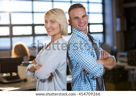 Portrait of confident male and female colleagues standing back to back in creative office - stock photo