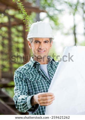 Portrait of confident male architect holding blueprint at construction site - stock photo