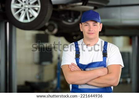 Portrait of confident male auto mechanic in workshop - stock photo