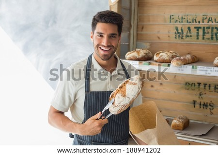 Portrait of confident male cafe owner with sweet food at coffee shop - stock photo