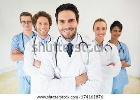 Portrait of confident male doctor with colleagues in hospital